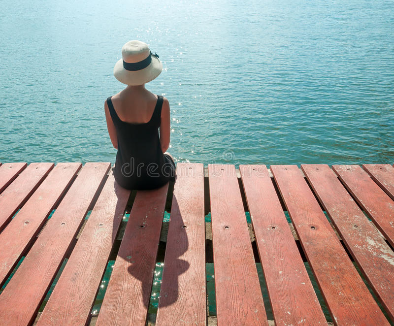 Girl waiting on the pier looking at ocean stock photos