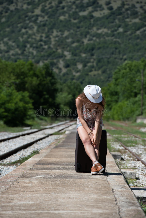 Girl waiting with rolling upright suitcase at docks. Pretty girl with curly hair wear casual clothes, sunglasses and panama hat, waiting with rolling upright royalty free stock photos