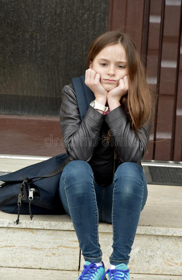 Girl is waiting for someone with front door key. Girl lost or forgot the latchkey, now she sits in front of the door and has to wait until her parents will come royalty free stock photos