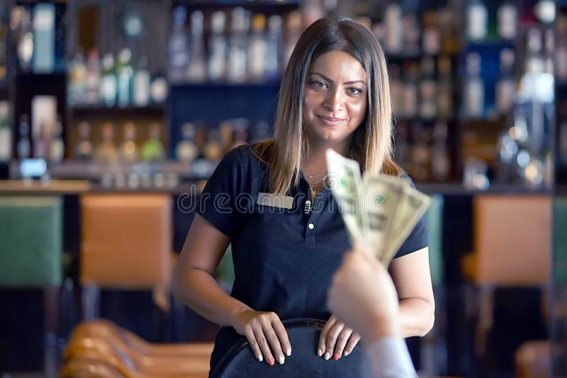 Girl of the waitress gets a tip. Waitress takes the tip. The waiter girl receives a tip from the client at the hotel bar. A bartender woman is happy to receive a stock images