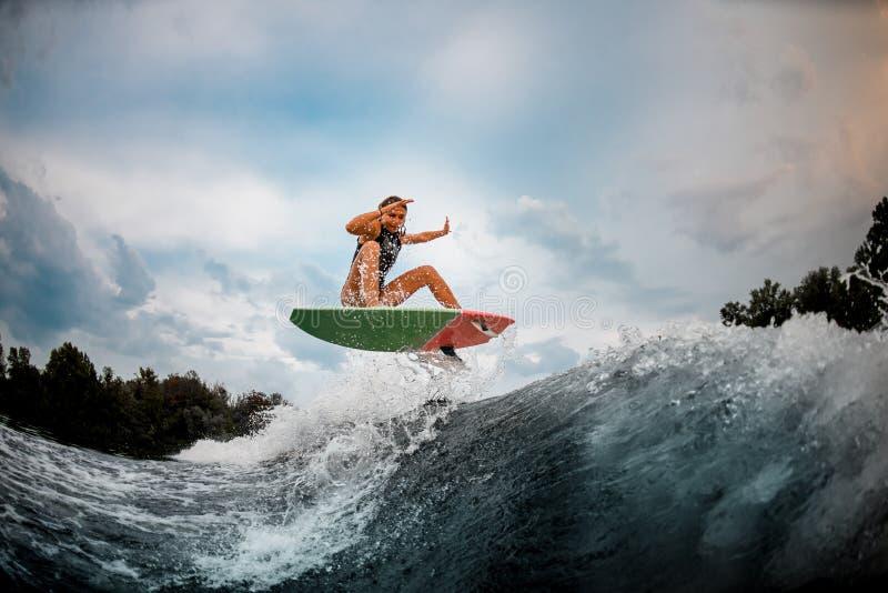 Girl wakesurfer springt met surfplank stock fotografie