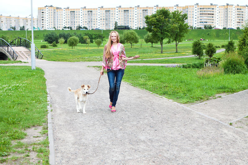 Girl walk with her puppy stock images