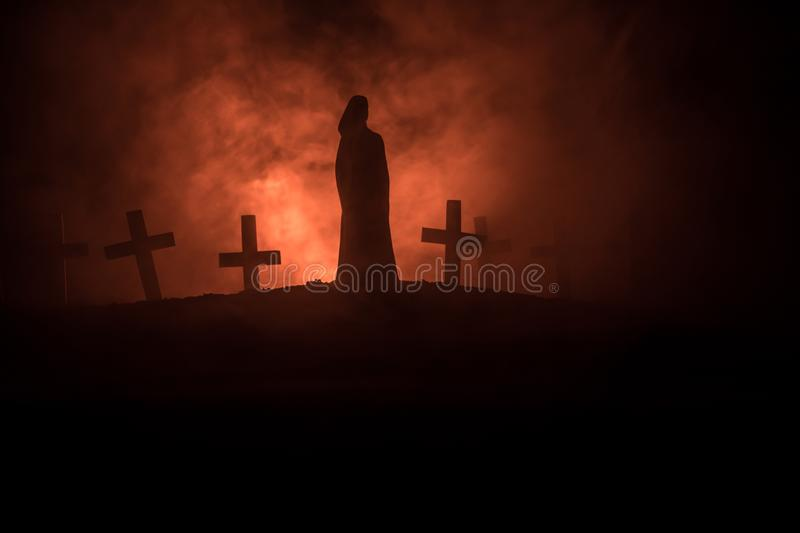 Girl walking alone in the cemetery at night. Dark toned foggy background. Horror Halloween concept stock photos