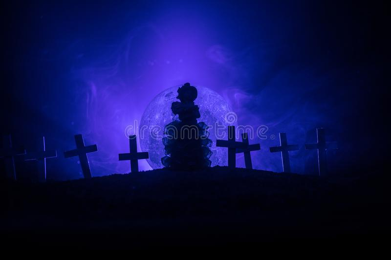 Girl walking alone in the cemetery at night. Dark toned foggy background. Horror Halloween concept royalty free stock images