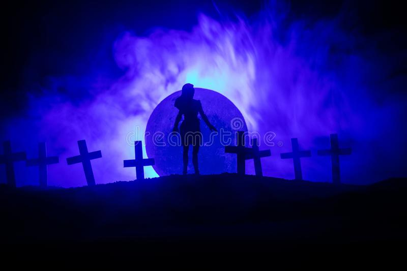 Girl walking alone in the cemetery at night. Dark toned foggy background. Horror Halloween concept royalty free stock photography