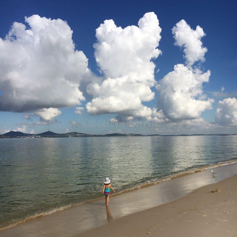 Girl walking along a deserted beach royalty free stock photo