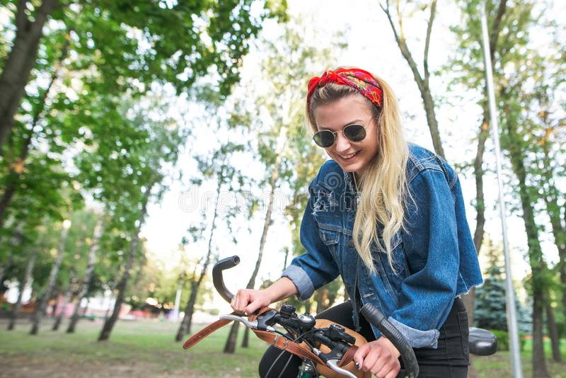Girl walking around the park and smiling. Smiling student girl in stylish clothes walking on a park bike ride stock images