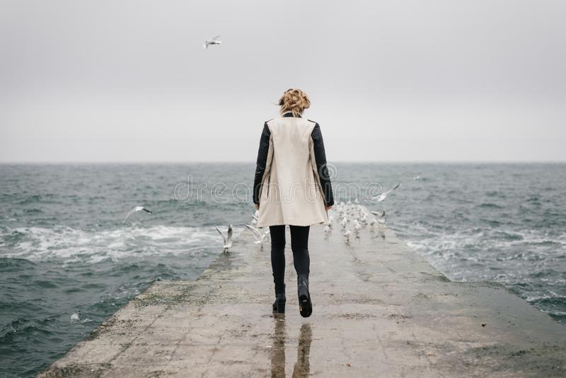 The woman is walking back on the pier and looking at the sea. royalty free stock images