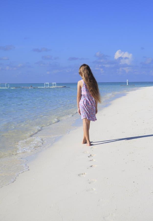 Girl walking on the beach royalty free stock photos