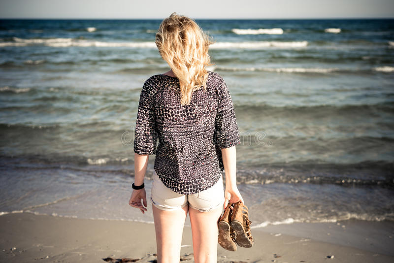 Girl walking at beach. Shoes in hand royalty free stock photos