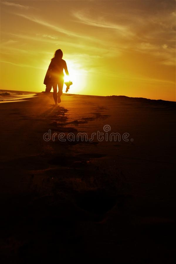 Girl walking on the beach in the sunset stock photography