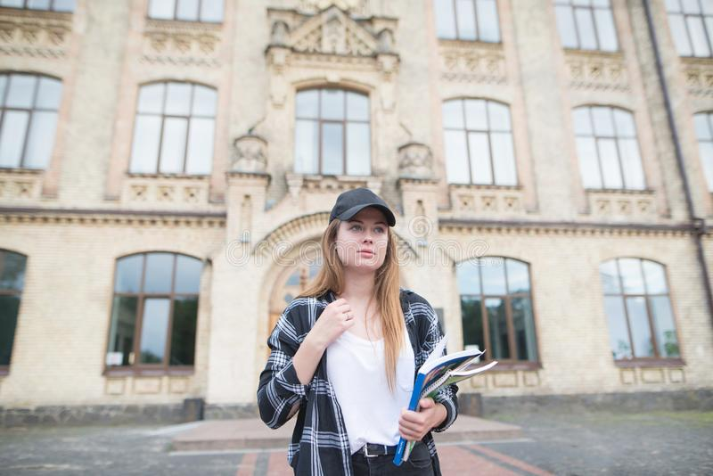 Girl walking on campus with books and books in his hands. Portrait of an attractive student in casual clothing royalty free stock photos