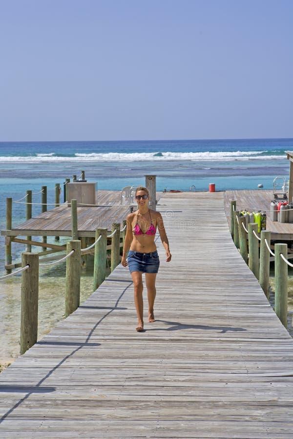 Girl walking on a Cayman Island Dock. Beautiful Girl walking on a Cayman Island Dock stock photos