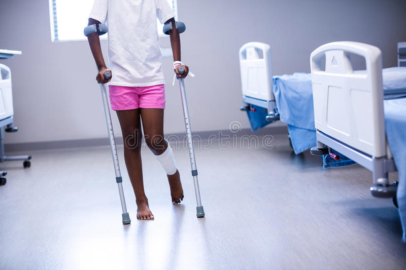 Girl walking with crutches in ward stock images