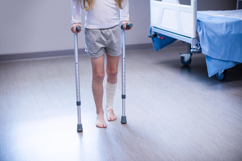 Girl walking with crutches in ward stock photo