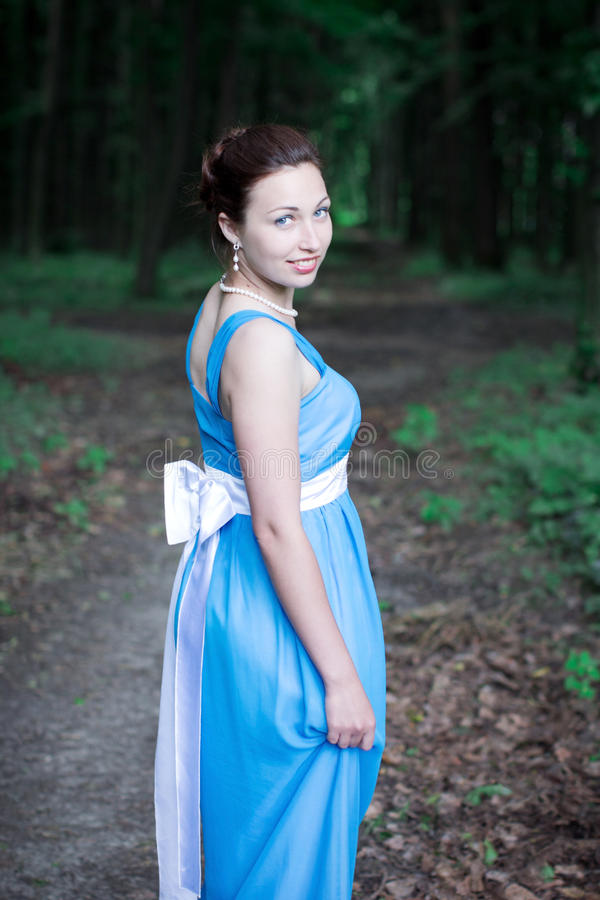 Girl walking on the dark green forest turns around royalty free stock photo