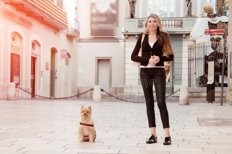 Girl walking with a dog in the city. Playful and lively Pomeranian dog. Faithful, friendly friend. Friendship concept. Dog royalty free stock photos