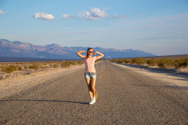 Girl walking down the endless road stock photos
