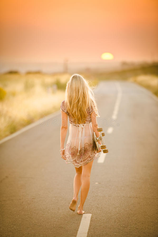 Girl walking with her skateboard royalty free stock image