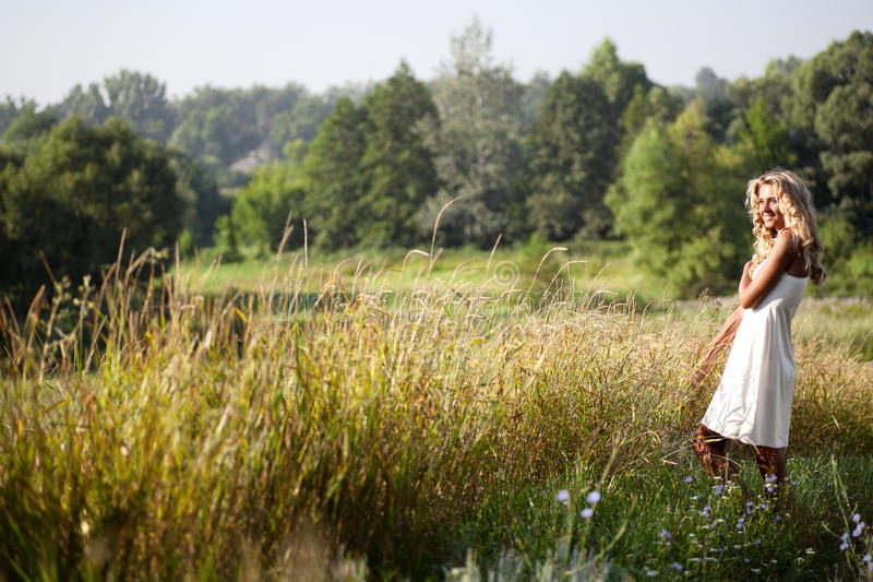 Girl walking on the meadow in summer day royalty free stock photos