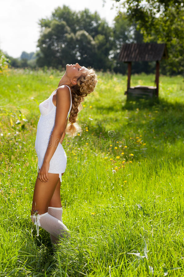 Girl walking on the meadow in summer day royalty free stock images