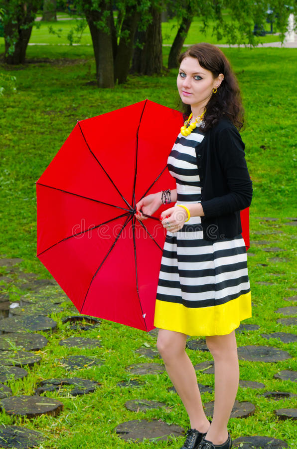 Girl walking after the rain. Girl walks in the park after the rain is holding a large red umbrella royalty free stock image