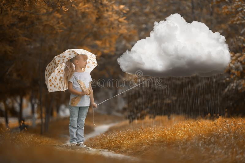 A girl walking the rainy cloud at autumn time on the orange background royalty free stock image