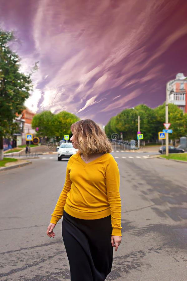 Girl walking on the road, looking at the sky royalty free stock photography