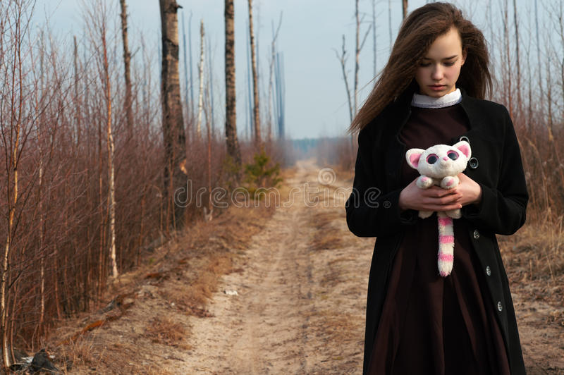 Girl walking on the road with toy in hands stock photo