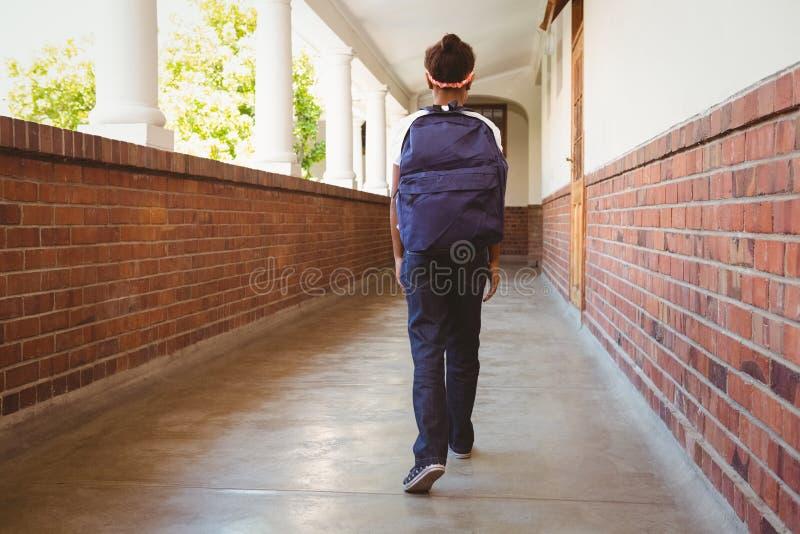Girl walking in school corridor stock image