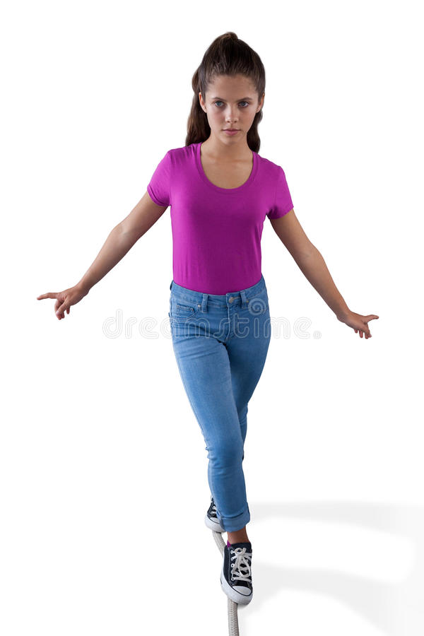 Girl walking on a tight rope and trying to keep her balance. Against white background stock images