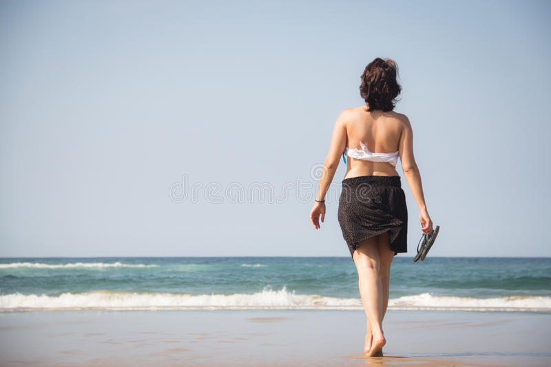 Girl walking towards the sea with flip flops in her hands. On the beach in Ponta Do Ouro in Mozambique royalty free stock photo