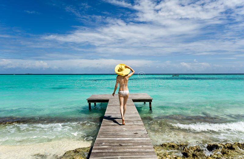Girl walking on wooden bridge extended into the se stock photos