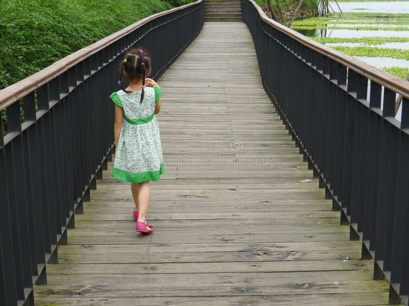Girl walking on the wooden footbridge royalty free stock images
