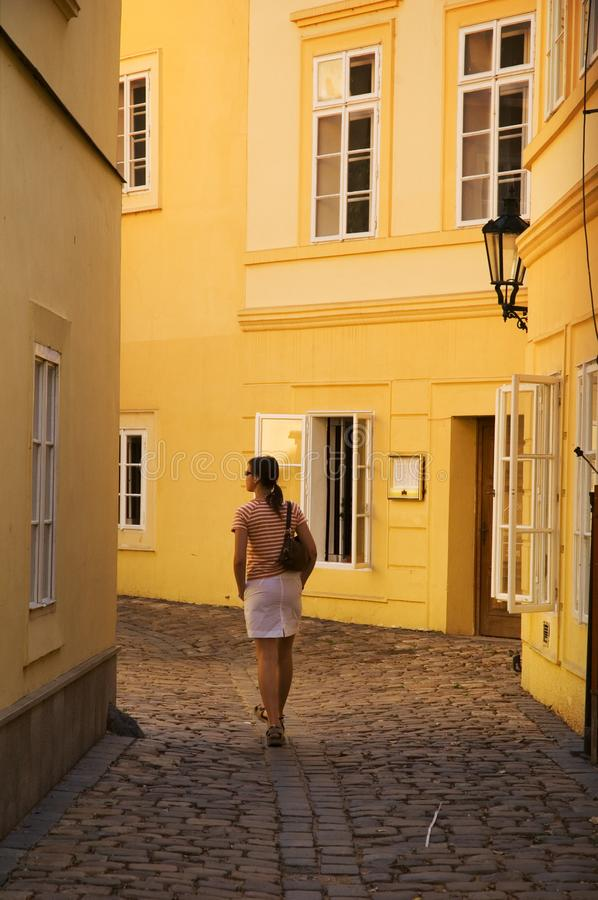 Girl walking between yellow buildings royalty free stock image