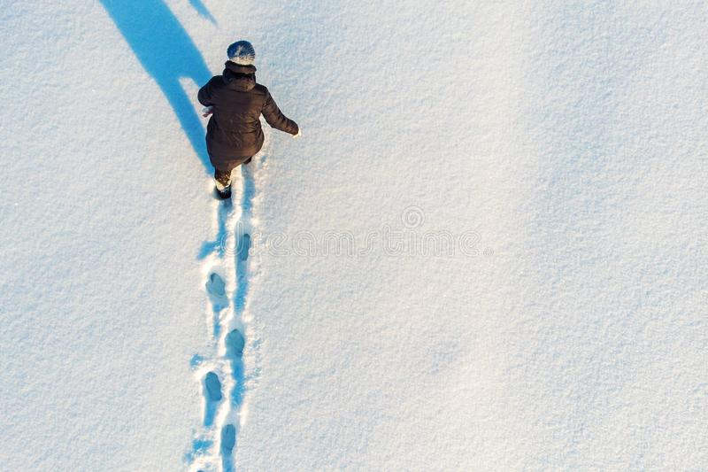 Girl walks or goes in snow leaving footprints, top aerial view. Winter outdoor activity background with copy space stock photography