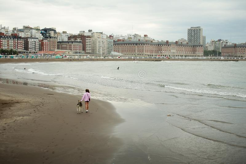 A girl walks her dog on the beach in Mar del Plata stock images