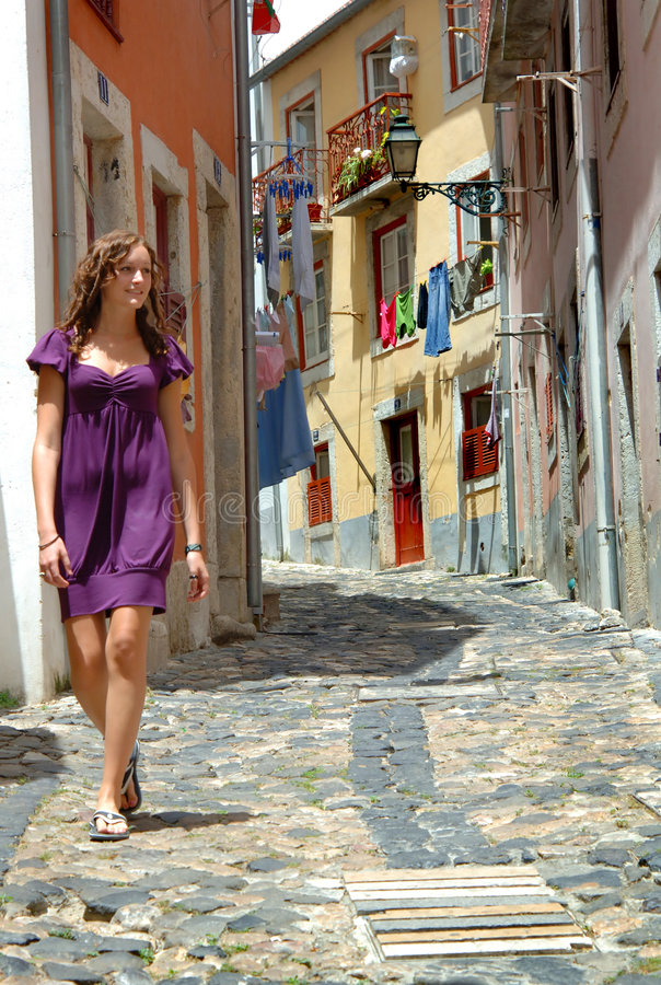 Girl walks portugal street. A pretty young woman walking on a colorful, narrow cobblestone street in Lisbon, Portugal stock photos