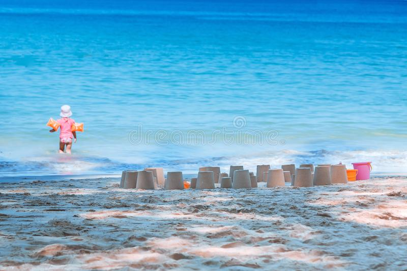 A girl walks into the water to swim. Made a lot of sand figures on the beach. Vacation with children by the sea. Summer time stock photos