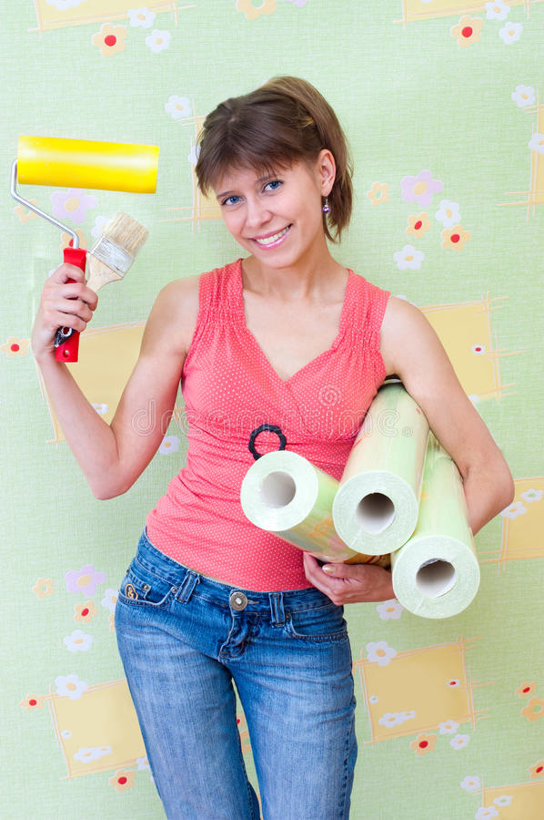 Girl wallpaper glues. The girl with the wallpaper in the hands of royalty free stock photos