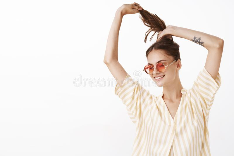 Girl wants comb hair for better comfort. Portrait of happy joyful attractive woman in stylish sunglasses and striped royalty free stock images