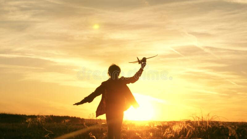 Girl wants to become pilot and astronaut. Slow motion. Happy girl runs with a toy airplane on a field in the sunset. Girl wants to become pilot and astronaut stock photography
