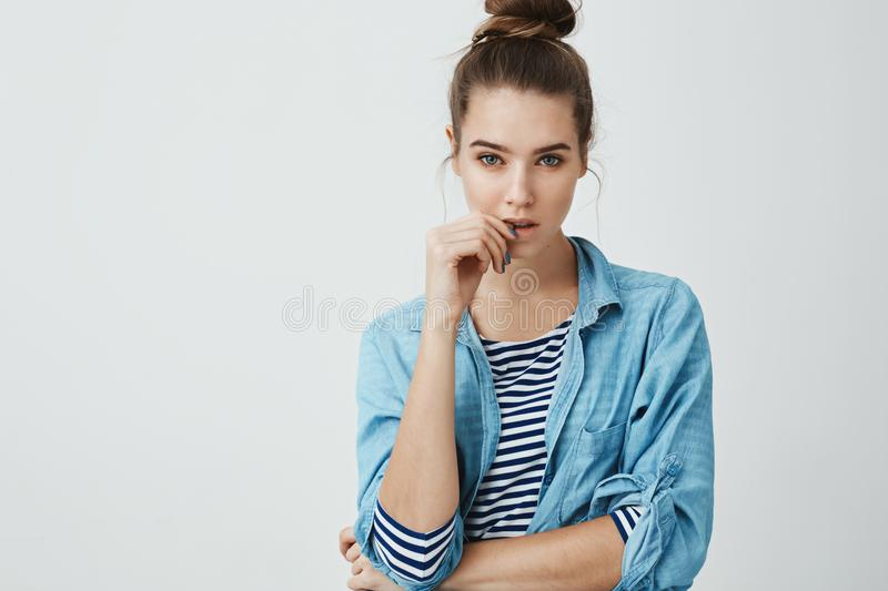 Girl wants to believe boyfriend but knows he is lying. Studio shot of suspicious focused woman with bun hairstyle stock image