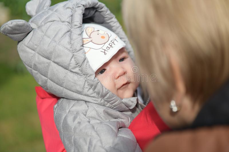 A girl in warm clothes on the street. A young and happy mother holds a baby in her arms, smiles and rejoices. Street in winter,. Fresh air, a boy up to a year royalty free stock images