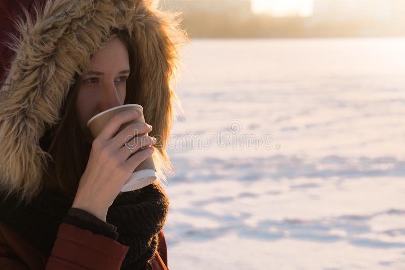 Girl in warm coat and hood having a hot drink on a cold day stock photography