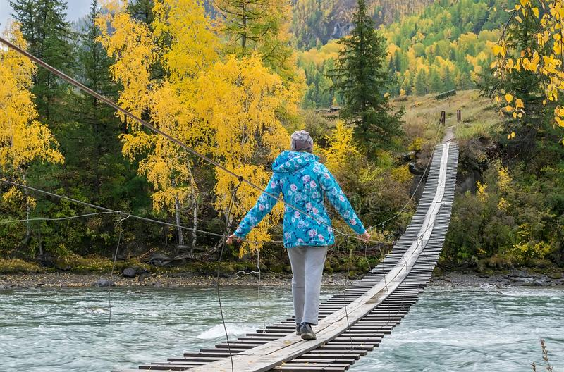 Girl in a warm jacket goes on a wooden suspension bridge on the other side of the turquoise river. Autumn mountain landscape w stock image