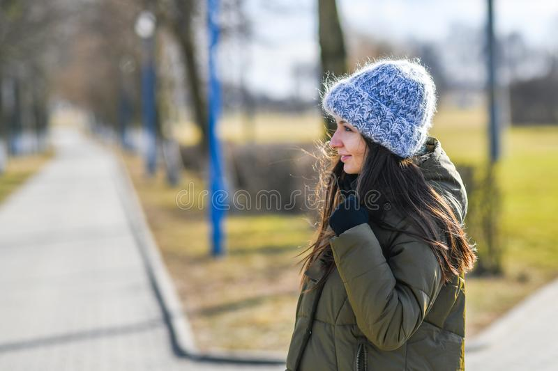 Girl in a warm knitted hat. Portrait of a beautiful young model in a gray knitted hat. walking down the street royalty free stock photo