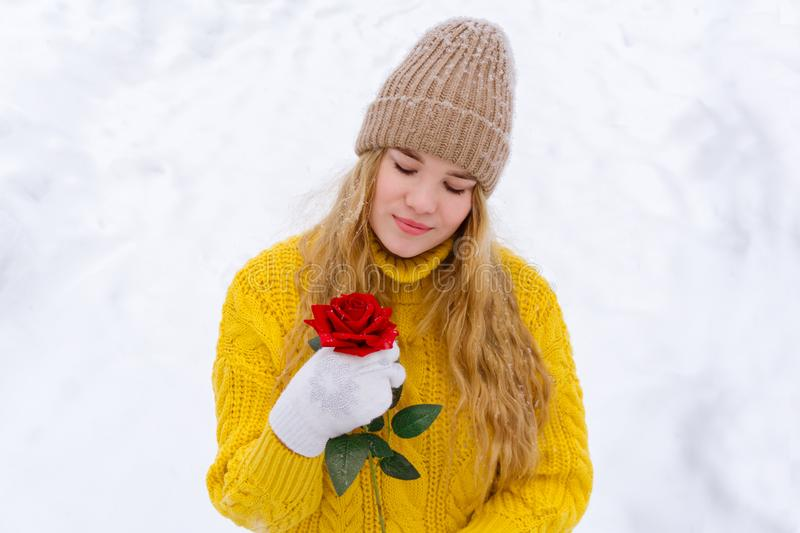 Girl with a rose on the background of snow royalty free stock photography