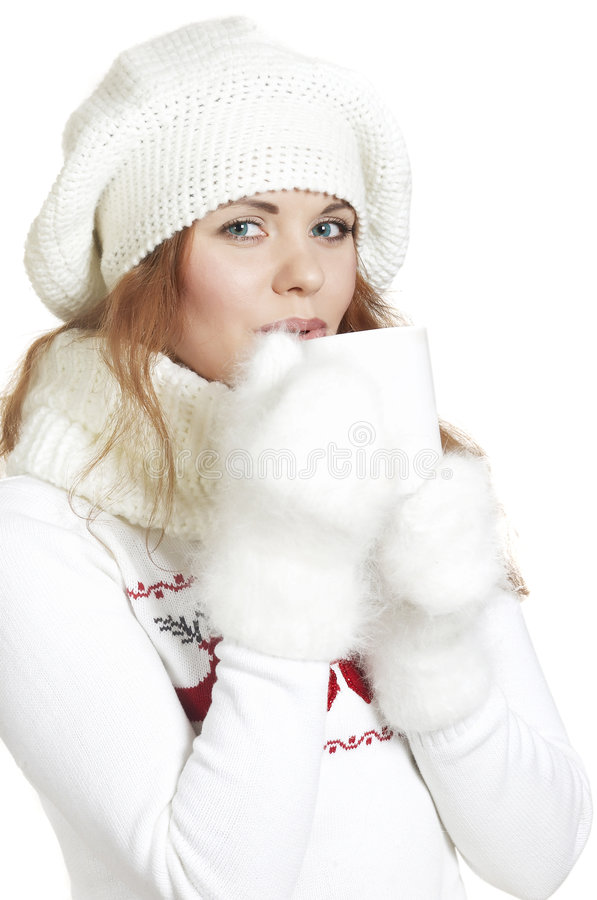 Girl is warmed by hot tea. The beautiful young woman in a white winter sweater stock images