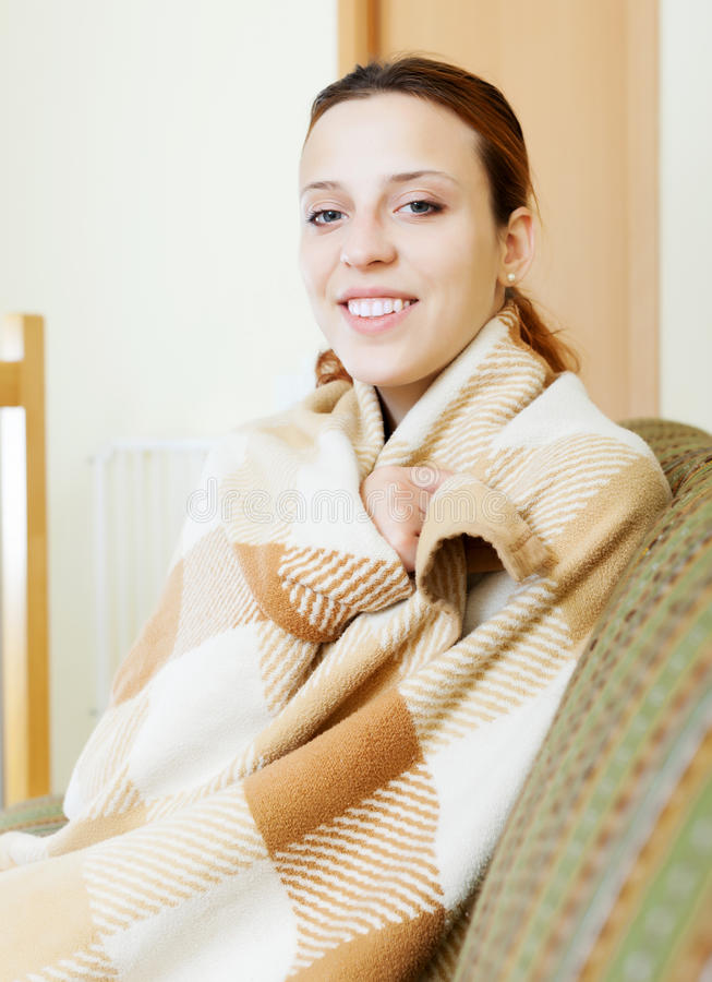Girl warming in plaid at home. In winter stock photos